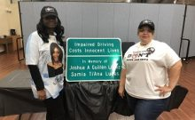 Carmen Lopez and Sherita Bussey with memorial sign