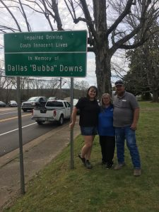 Parents and Nana with sign