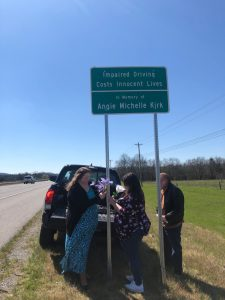 Vicki and Donna put flowers on highway sign