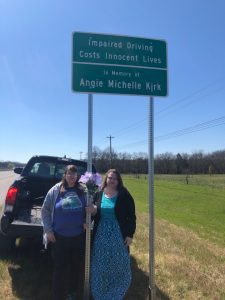 Vicki Kirk and sister with highway sign