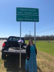 Vicki Kirk with roadside sign for Angie Michelle Kirk