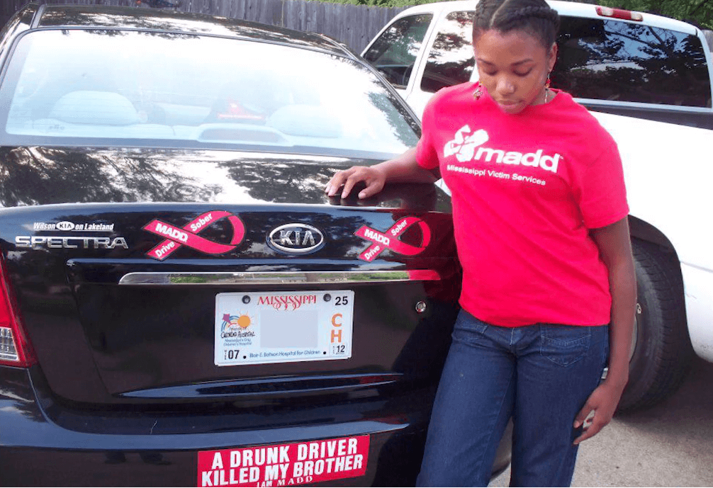 Prisca with the MADD bumper sticker her parents gave her when she got her first new car.